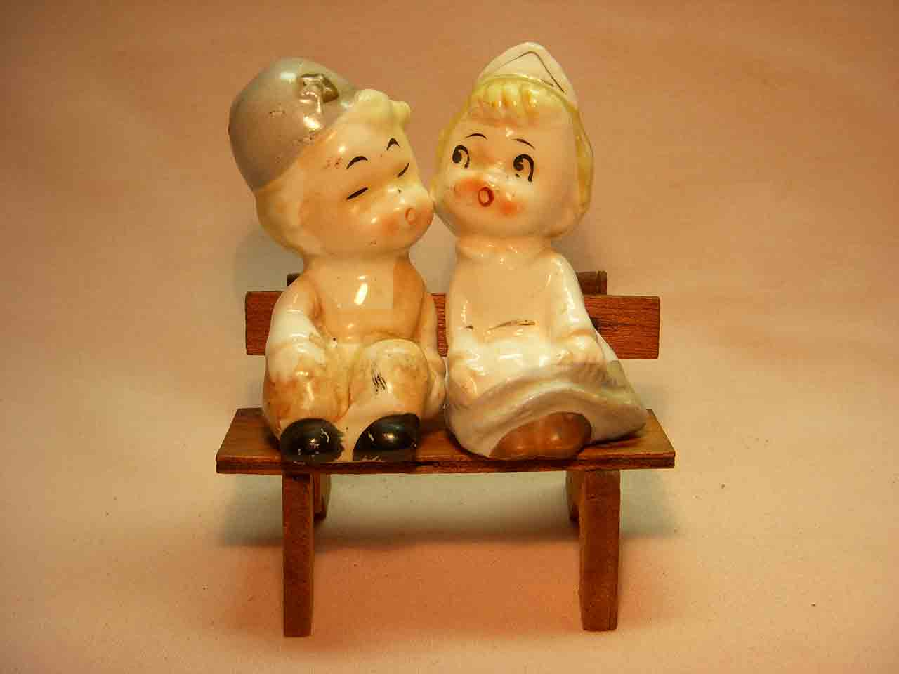 Little boy and nurse girl sitting on wooden bench salt and pepper shaker