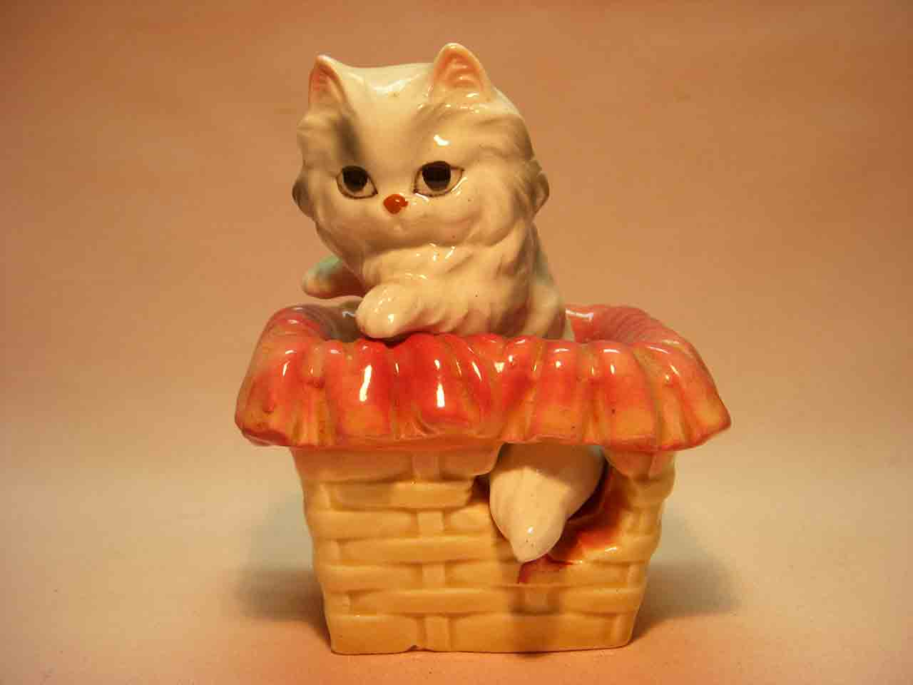 Nester cat sitting inside a basket salt and pepper shaker