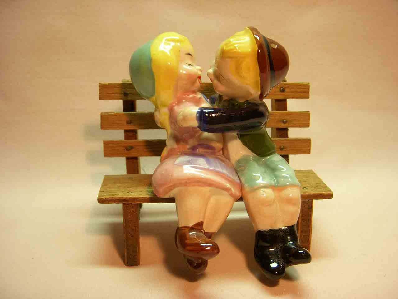 Boy and girl kissing sitting on wooden bench salt and pepper shaker